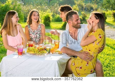 Young Beautiful Teenager Friends Enjoying Picnic On Party Outdoor In Park.