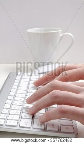 Fingers Close Up Typing. Fingers Are Typing On The Keyboard, With White Coffee Mug On The Background