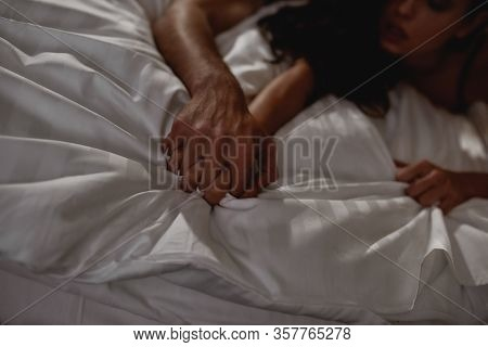 Young Couple Making Love In The Bed. Tender Lovers Holding Hands, Fingers Intercrossed. Desire, Love