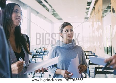 Excited Newcomers Listening To Trainer Or Mentor. Young Women In Casual Standing In Training Room, H
