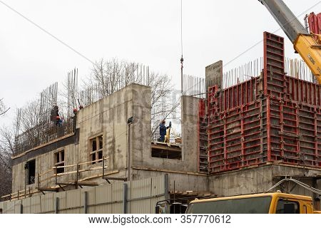 Moscow, Russia - January 7, 2020: Construction Of An Office Building. Construction Workers In Overal