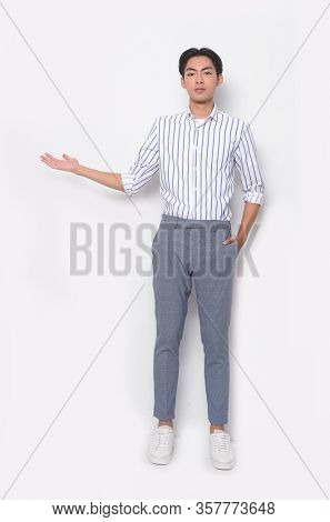 full length young man in wearing long sleeve striped shirt with gray pants presenting and pointing with palm of hand standing on white background