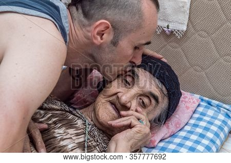 Grandson Kissing His Grandma's Face, Showing His Respect And Love