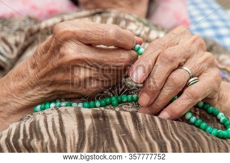 Close Up Of Old Female Hands Holding Green Praying Beads. Belief Concept.