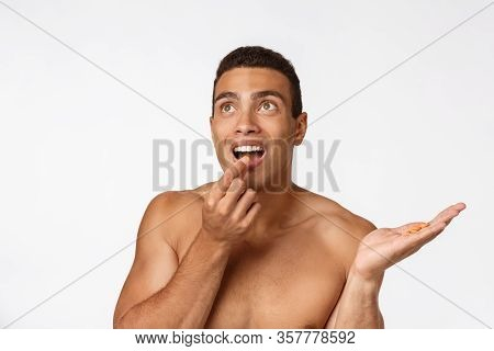 Sick African American Guy Eating Medicine Pill. Black Man Standing On Plain Background With Copy Spa