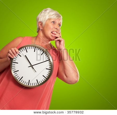 Senior Woman Holding A Clock And Thinking On Green Background