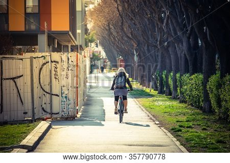 Rear View Of A Woman Riding A Bycicle On The Pavement On The Streets Of Split, Croatia. Sidewalk In