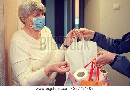 An Elderly Woman In A Medical Mask Stays At Home Isolated. Food Delivery To The Elderly.
