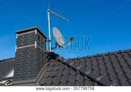 Vintage Analog And Modern Digital Satellite Dish Antenna On A House Roof. Ceramic Tiles.