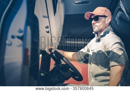 Caucasian Men Driving Semi Truck. Trucker In His 30s Inside Semi Tractor Cabin.