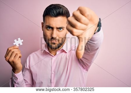 Young handsome businessman holding piece of puzzle over isolated pink background with angry face, negative sign showing dislike with thumbs down, rejection concept
