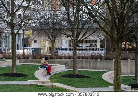 Reston, Va, Usa -- March 26, 2020.  A Man Sits Alone  With His Yoga Mat And Gym Bag In Reston Town C