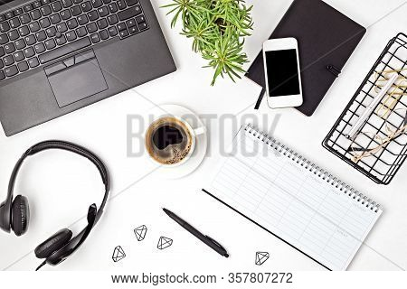 Top View Of Office Desk. Table With Laptop, Conference Speakerphone And Office Supplies. Flat Lay Ho