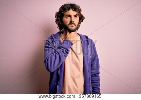 Young handsome sporty man with beard wearing casual sweatshirt over pink background Touching painful neck, sore throat for flu, clod and infection