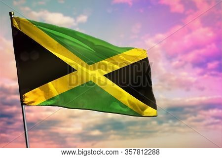 Fluttering Jamaica Flag On Colorful Cloudy Sky Background. Jamaica Prospering Concept.
