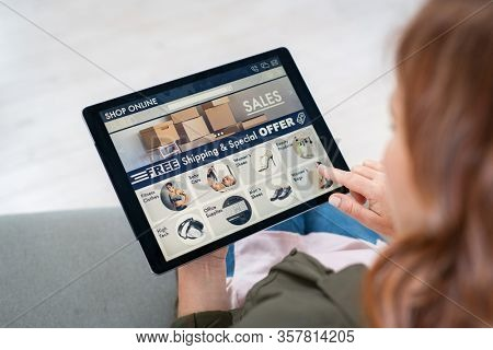 Back view of woman doing shopping online on website with digital tablet at home. Top view of lady on relaxing sofa. Rear view of girl hand touching screen while selecting product on e-commerce portal.