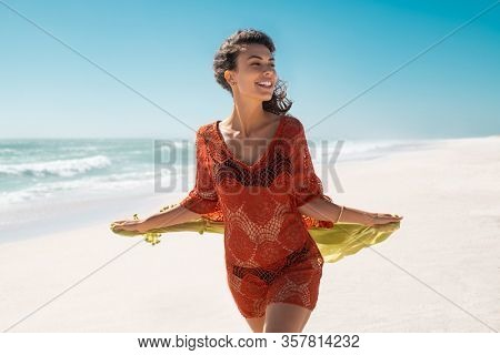 Beautiful smiling woman walking on the beach with a green scarf, seaside in background. Happy stylish and active girl flying tissue and enjoying summer vacation while wearing red fashion crochet dress