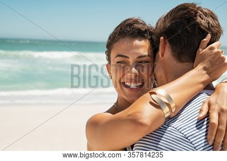 Close up face of happy young woman embracing her boyfriend at the beach while laughing, copy space. Portrait of girl hugging man at sea. Cheerful couple hugging and smiling while relaxing at vacation.