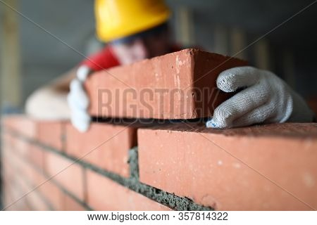 Close-up Of Professional Construction Worker Laying Bricks In Industrial Site. Builder In Protective