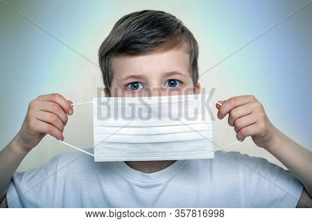 Studio portrait of a boy in a mask on a gray background. Concept of fight against the coronavirus epidemic and proper prevention of infections
