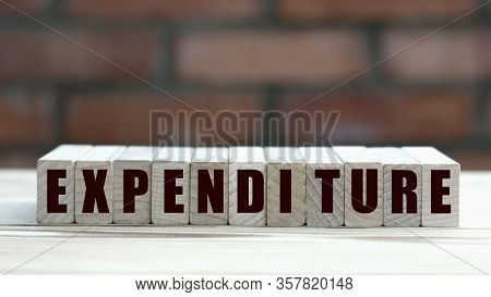 Concept Word Expenditure On Cubes Against The Background Of A Brick Wall