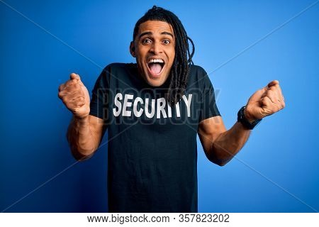 Young african american afro safeguard man with dreadlocks wearing security uniform screaming proud and celebrating victory and success very excited, cheering emotion