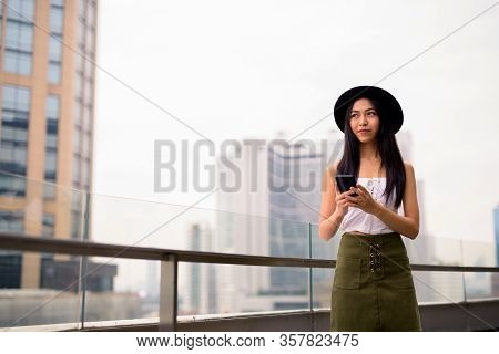 Young Beautiful Asian Tourist Woman Thinking While Using Phone Against View Of The City