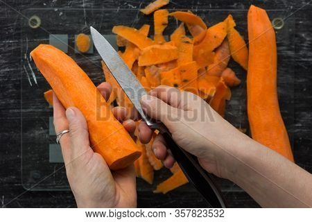 Top View Of Woman Hands Holding Peeled Carrot And Knife On Glass Cutting Board With Peeling On The B