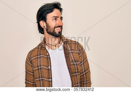 Young handsome hispanic bohemian man wearing hippie style standing over isolated background looking away to side with smile on face, natural expression. Laughing confident.