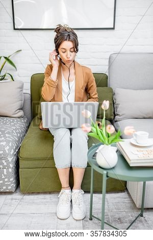 Young Business Woman Working On Computer, Talking Online Using A Headset While Sitting On The Comfor