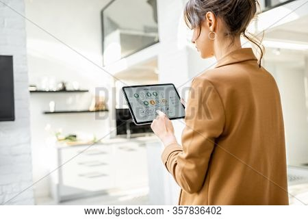 Woman Controlling Smart Home Devices Using A Digital Tablet With Launched Application In The White L