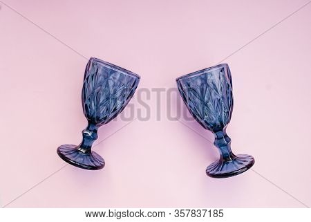 Two Blue Faceted Glasses On A Pink Background