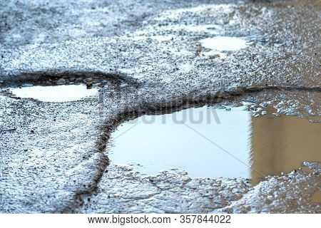 Close Up Of A Road In Very Bad Condition With Big Potholes Full Of Dirty Rain Water Pools.