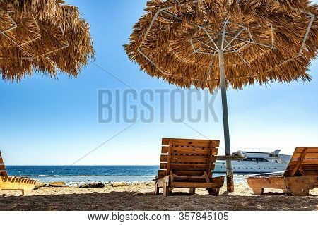 Wooden Deck Chairs Under Rough Straw Sun Umbrella On Sea Beach And Big White Yacht Ship In Water Nea