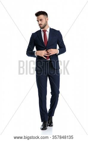 handsome businessman wearing navy suit walking while opening his jacket and looking aside with tough attitude on white studio background