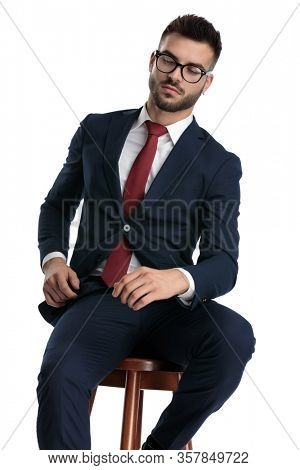 young businessman wearing glasses sitting and posing tough on white studio background