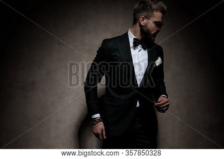 young businessman wearing sunglasses standing with loose hands and looking aside dramatic on dark studio background