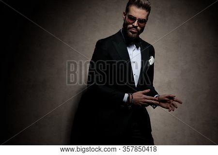 young businessman wearing sunglasses standing with hands to aside and striking a pose with tough attitude on dark studio background
