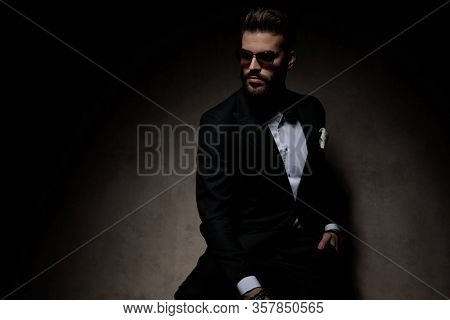 sexy businessman wearing sunglasses sitting with hand in pocket and looking away tough on dark studio background