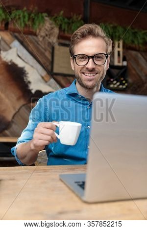 young casual man wearing glasses sitting at desk and working on laptop while drinking his cup of coffee and looking at camera happy at the coffeeshop
