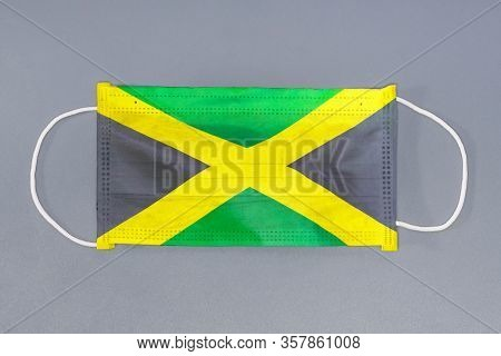 Isolated Medical Mask With Flag Of Jamaica On Gray Background. Closeup Protective Masks Textile Filt