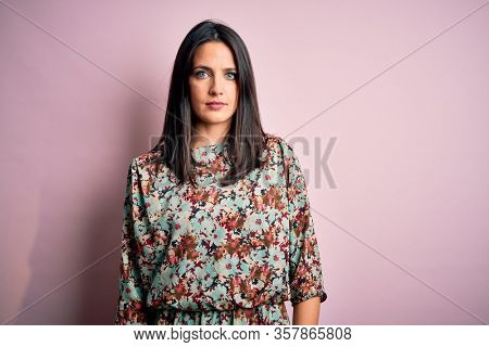 Young brunette woman with blue eyes wearing floral colorful dress over pink background with serious expression on face. Simple and natural looking at the camera.