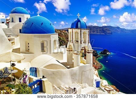Iconic Santorini - most beautiful island in Europe. view with traditional blue churches in Oia village. Greece, Cyclades