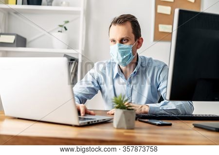 Viral Threat, Seasonal Viral Diseases. A Man Works In The Office In A Medical Mask, Protecting Offic