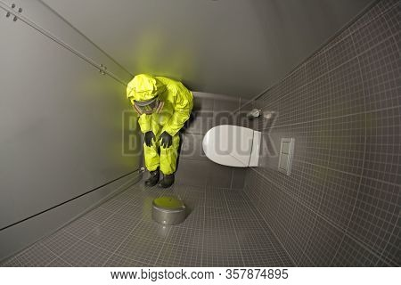 Quarantine - overhead view of man in protective coverall sitting  in the toilet and waiting.