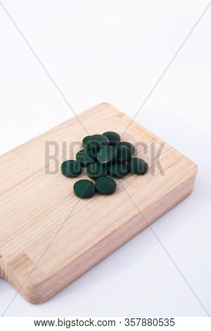 Spirulina Tubs On A Light Brown Wooden Cutting Board. Healthy Lifestyle. Place For A Text. Closeup.