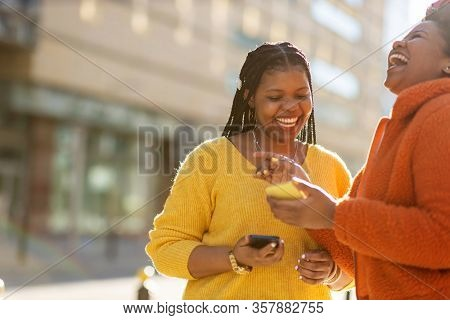 Happy female friends sending messages with their smartphones in the city