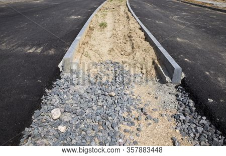 Small Rubble And A Layer Of Asphalt At The Construction Site Of A New Highway Or Roadway