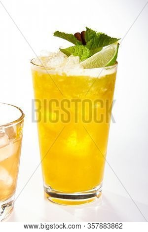 Mai Tai cocktail close up. Alcohol long drink in glass side view. Refreshment tropical beverage with rum, passion fruit, lime and mint. Exotic cocktail with crushed ice and citrus glassware