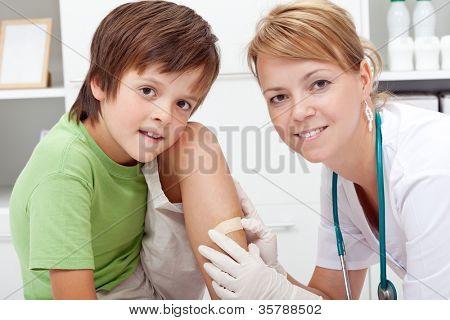 Putting a bandaid on wound - boy in emergency room